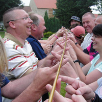 team having great fun with the Helium Stick team building activity